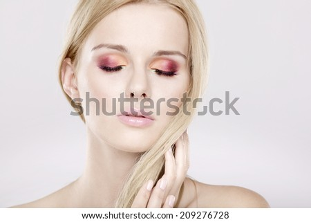 Portrait of young adult pretty woman with beautiful blond hairs and multicolor makeup isolated on white background