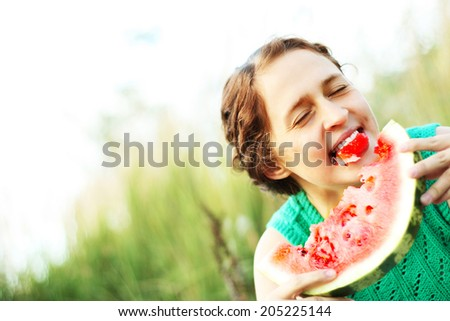 Portrait of Young adult redhead caucasian laughing girl with watermelon on blurred green forest background Empty Copy space for inscription - stock photo