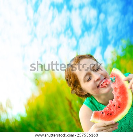 Portrait of Young adult redhead caucasian laughing girl with watermelon on blurred green forest blue sky with clouds background Empty Copy space for inscription - stock photo