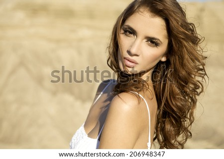 portrait of young adult sensuality brunette girl over sand background