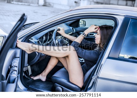 Portrait of Young adult sexy brunette dream about handsome man girl sitting in luxury black sport car Slim cute asian woman inside black leather chair auto open door with leg Hand on face Wait on date - stock photo