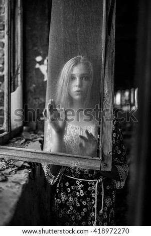 portrait of Young adult woman sit on windowsill near dirty glass window. wooden old vintage retro aged frame. white and black  - stock photo