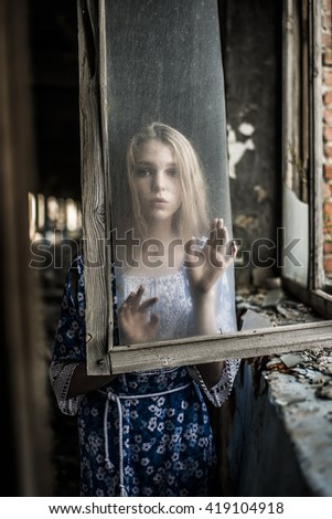 portrait of Young adult woman sit on windowsill near dirty glass window. wooden old vintage retro aged frame.  - stock photo