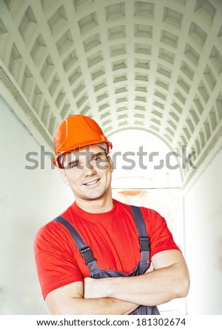 Portrait of young adult worker in blue and red uniform and security orange helmet standing above green arch building in perspective background  - stock photo