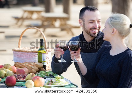 Portrait of young adults drinking wine at table in nature  together - stock photo