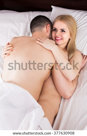 Portrait of young adults making love in bedroom - stock photo