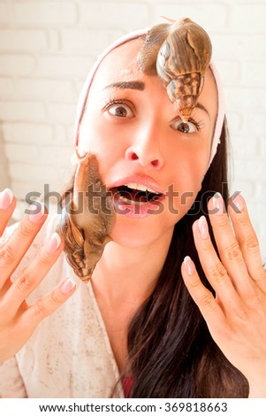 portrait of young afraid darkhaired woman with snails achatina giant on her face