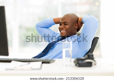 portrait of young african american businessman relaxed in office - stock photo