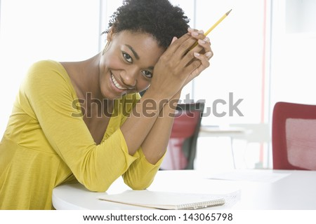 Portrait of young African American businesswoman with notepad and pencil sitting at table - stock photo