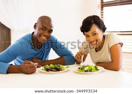 portrait of young african american couple eating healthy salad for lunch - stock photo