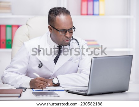 Portrait of young African American doctor at work, with laptop. - stock photo