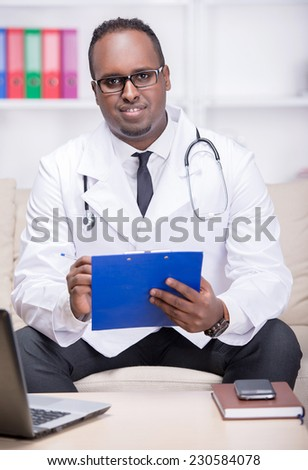 Portrait of young African American doctor is sitting in his office. - stock photo