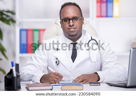Portrait of young African American doctor is sitting in his office.