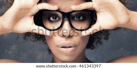 Portrait of young african american girl with afro, wearing fashionable eyeglasses, looking at camera. Studio shot.
