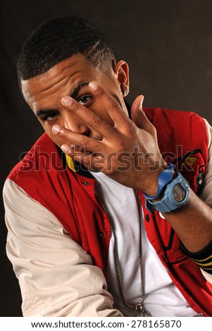 Portrait of young African American hip hop man with hand in front of face - stock photo