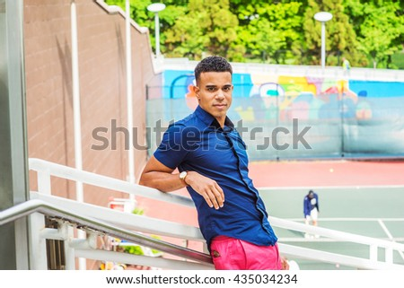 Portrait of Young African American Man in New York. Wearing blue short sleeve shirt, arm resting on railing, a college male student standing by tennis court on campus, relaxing, taking break.  - stock photo