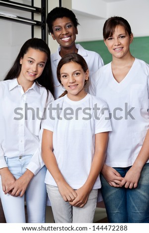 Portrait of young African American teacher with female students standing together in science lab