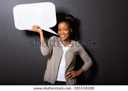 portrait of young african american woman with blank speech bubble isolated on black - stock photo