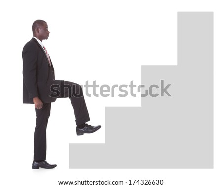 Portrait Of Young African Businessman Climbing Steps On White Background - stock photo