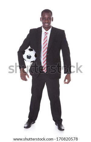 Portrait Of Young African Businessman Holding Football - stock photo
