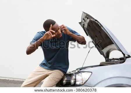 Portrait of young african guy standing in front of a broken car and making a phone call for help - stock photo