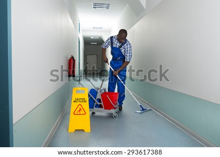 Portrait Of Young African Male Janitor Cleaning Floor In Corridor - stock photo