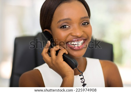 portrait of young african office worker using telephone in office - stock photo
