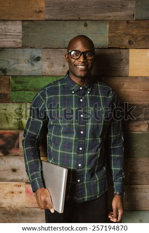 Portrait of young african student with laptop smiling at camera. Bald young man wearing glasses standing against a wooden wall. - stock photo