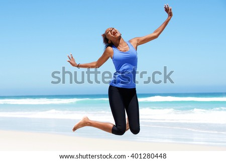 Portrait of young african woman jumping with joy at the beach - stock photo