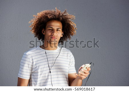 Portrait of young afro man with earphones and cellphone