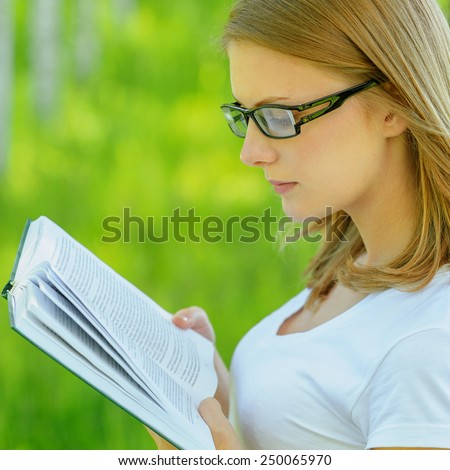 Portrait of young alluring blonde woman holding book, wearing white clothes and eyeglasses, standing at summer green park. - stock photo