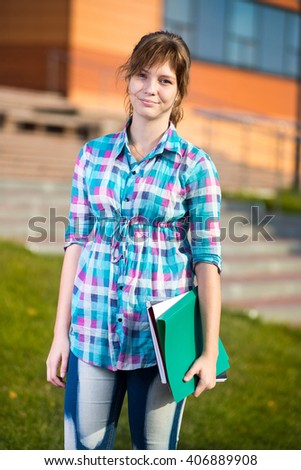 Portrait of young alluring woman holding education books. Standing at summer college park. Student girl. - stock photo