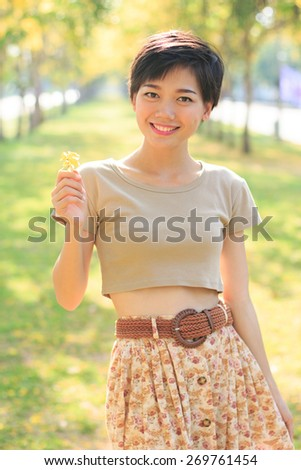 portrait of young and beautiful asian woman standing in park with little flowers in hand smiling to camera happiness emotion - stock photo