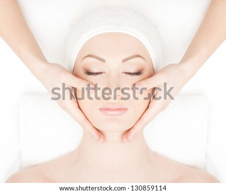 Portrait of young and beautiful woman getting spa treatment isolated on white - stock photo