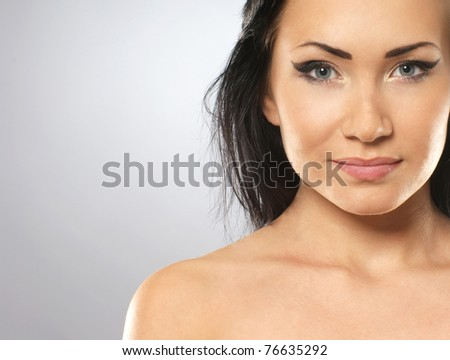 Portrait of young and fresh asian brunette over grey background