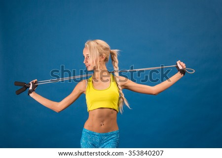 Portrait of young and healthy blonde with skipping rope over the blue background