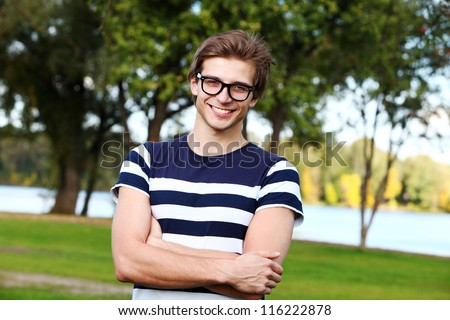 Portrait of young and smiling cute man with glasses in park - stock photo