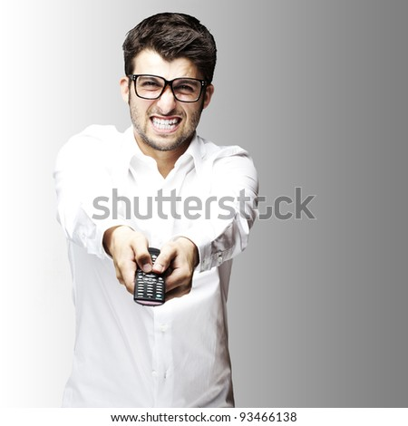 portrait of young angry man holding control tv over grey background - stock photo