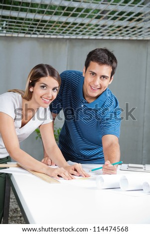 Portrait of young architects working on blueprints together