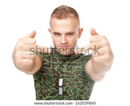 Portrait of young army soldier showing the middle fingers isolated on white background