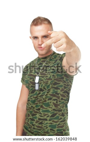 Portrait of young army soldier showing the middle fingers isolated on white background. Focus on finger