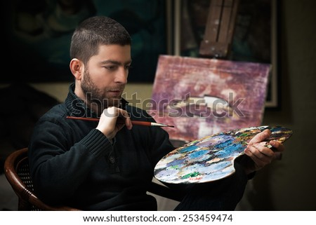 Portrait of young artist holding art palette and paintbrush while creating new artwork in his studio. - stock photo