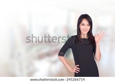 Portrait of young asia business woman showing ok sign in gym background.Mixed Asian / Caucasian businesswoman.Positive emotion - stock photo
