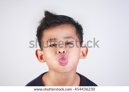 Portrait of young Asian boy sticking out his tongue mocking gesture - stock photo