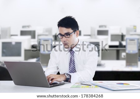 Portrait of young asian businessman typing on laptop computer shoot at office - stock photo