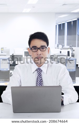 Portrait of young asian businessman working with laptop computer shoot at office - stock photo