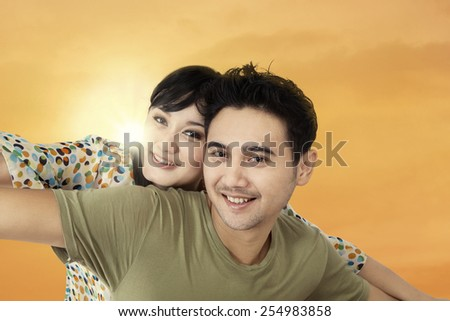 Portrait of young asian couple cuddling to enjoy freedom at sunset time - stock photo