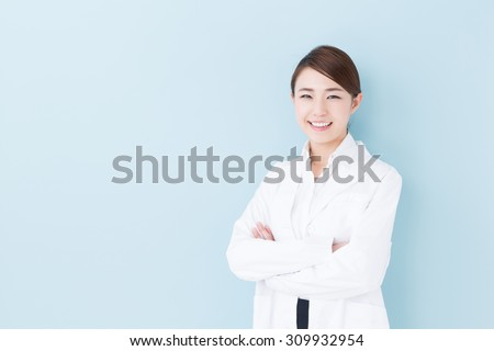 portrait of young asian doctor isolated on blue background - stock photo