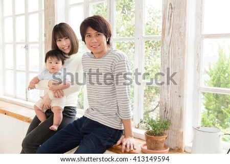 portrait of young asian family relaxing in room - stock photo