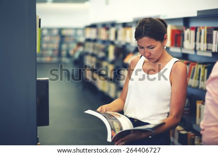 Portrait of young asian female holding open magazine or book while standing near bookshelves, attractive chinese student girl read book in university library, female freelancer in co-working space